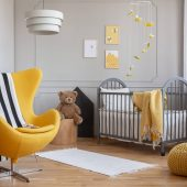 yellow-armchair-teddy-bear-and-crib-in-a-modern-ki-F5JHBNQ-scaled.jpg